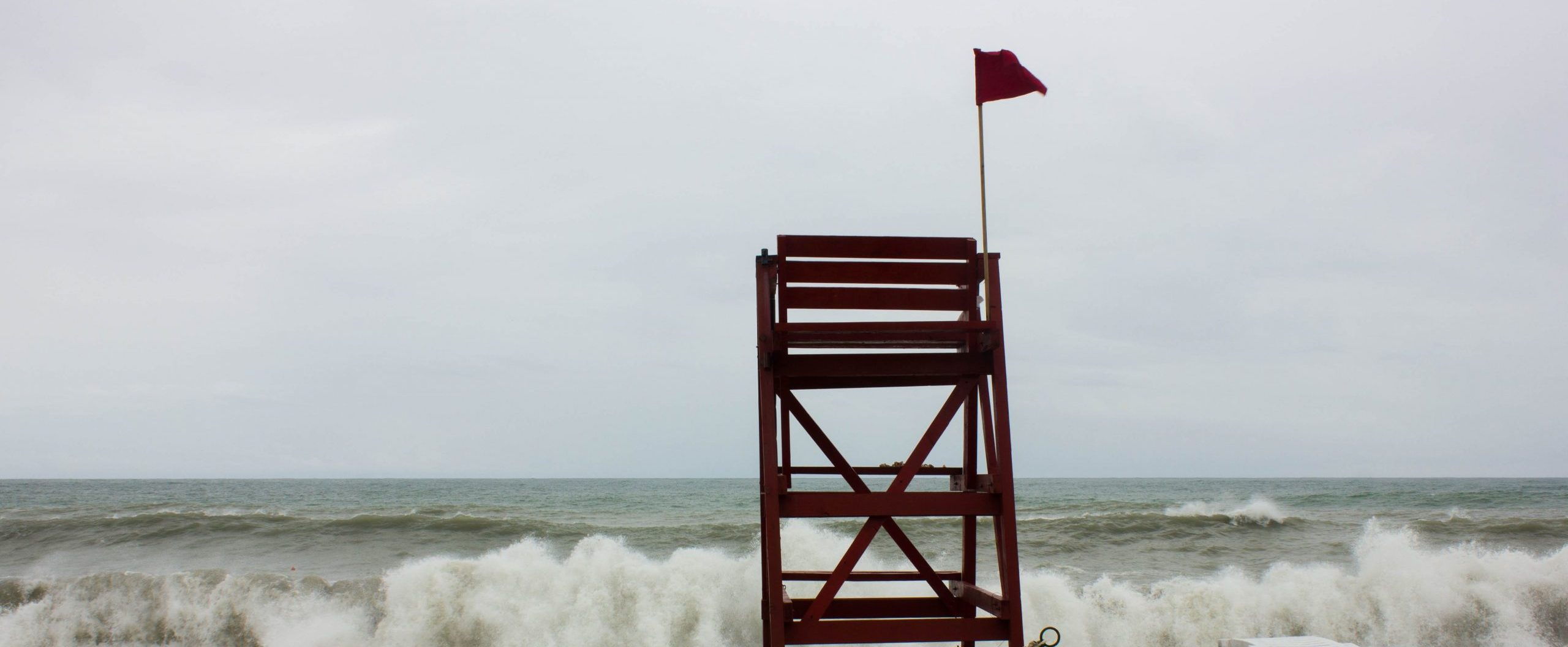 Red flag on a stormy beach