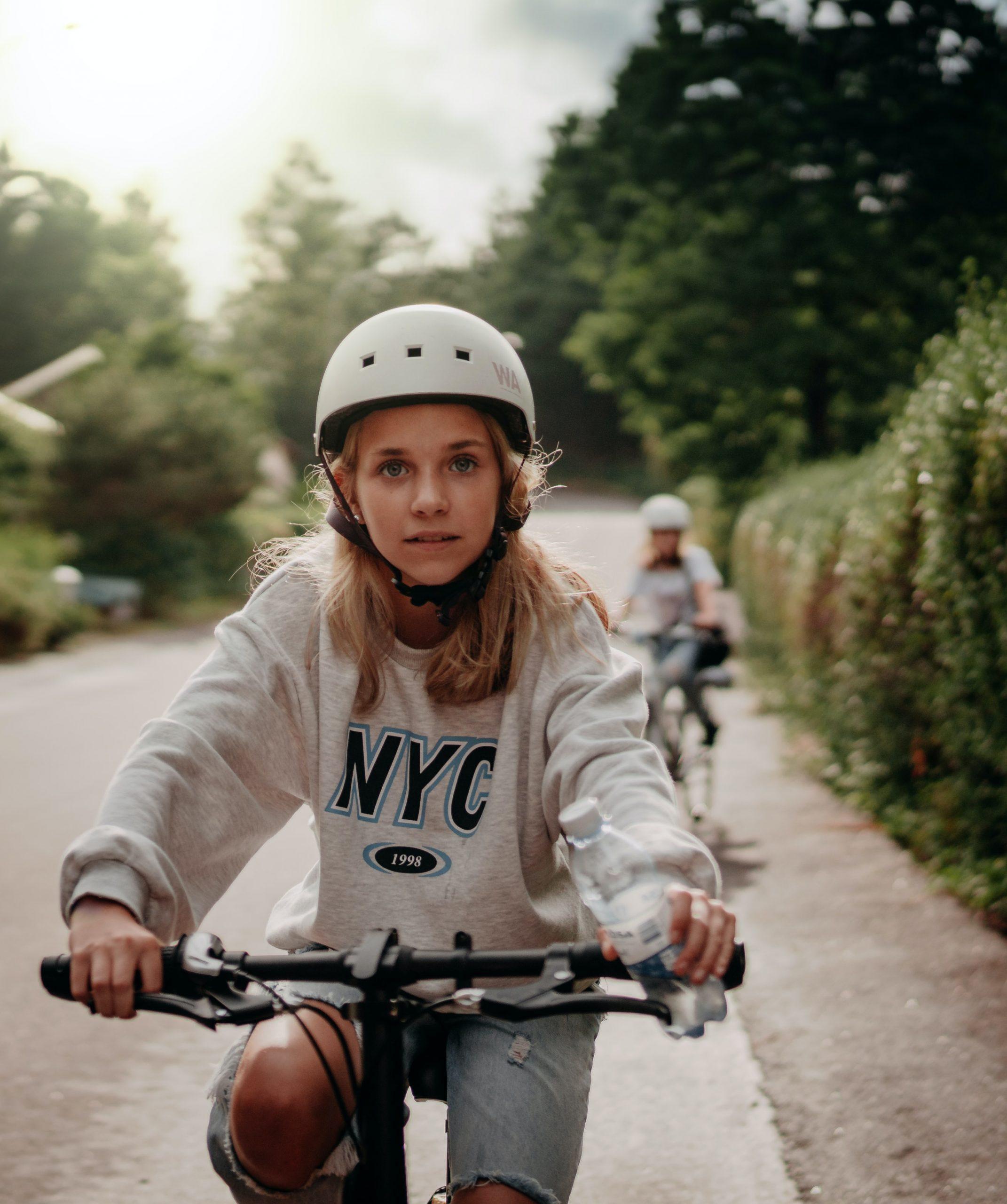 girl biking with a helmet on
