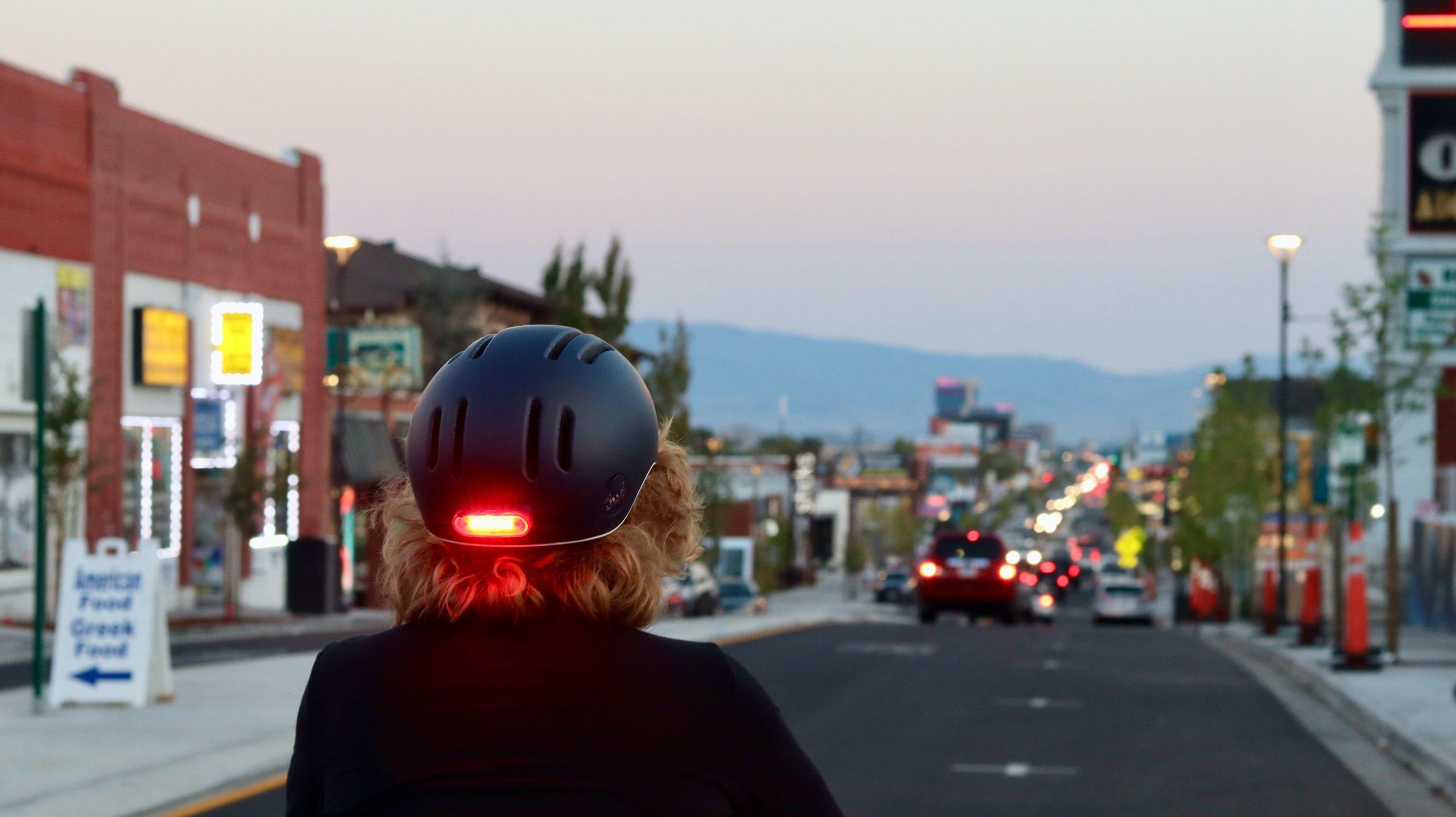 Girl biking with a lit helmet